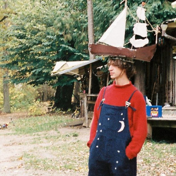 Musician Cosmo Sheldrake standing in a forest wearing a boat hat