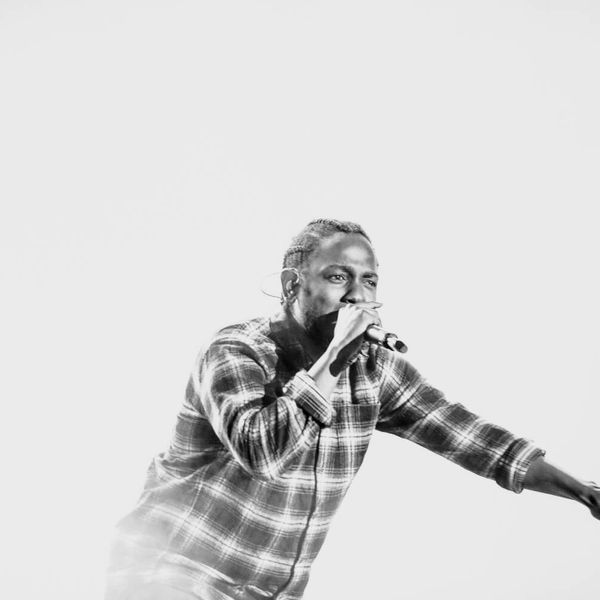 Black and white photograph of Kendrick Lamar performing onstage