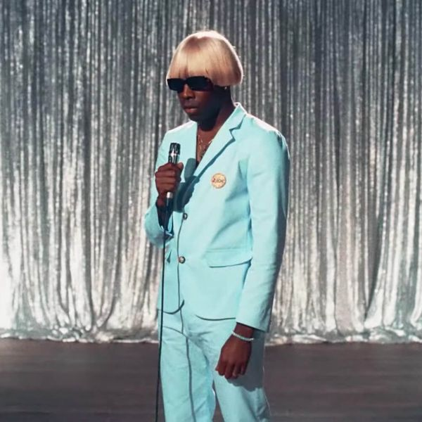Tyler, the Creator wearing a dashing baby blue suit and monstrous blonde wig