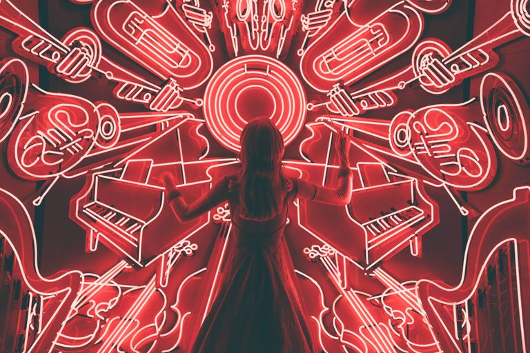 Girl standing in front of musical themed neon signs