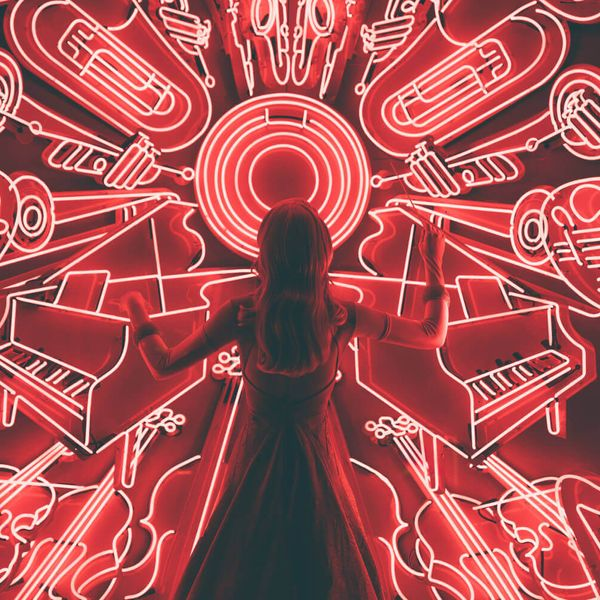 Woman standing in front of musically themed red neon signs