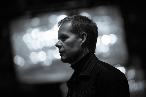 A monochrome shot of Max Richter standing looking to the left.