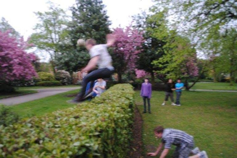 A group stands in a park as a person jumps over a hedge